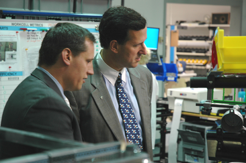 Justin McElhattan, President, Industrial Scientific Americas (left), explains some of the company's most recent developments in lean manufacturing operations to Sen. Rick Santorum.