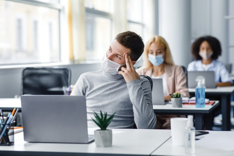 Creative ideas and brainstorming during work. Guy in protective mask thinks and looks out the window, sitting at table with laptop with antiseptic in office interior with colleagues