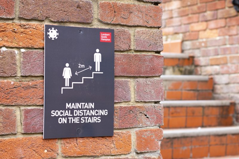 COVID 19 safety information sign for shoppers mounted on brick w