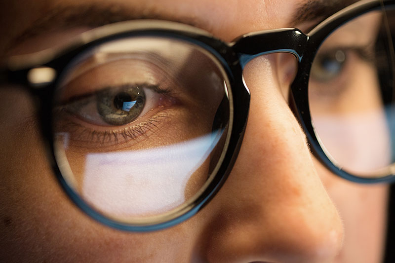 close up of woman in glasses looking at screen