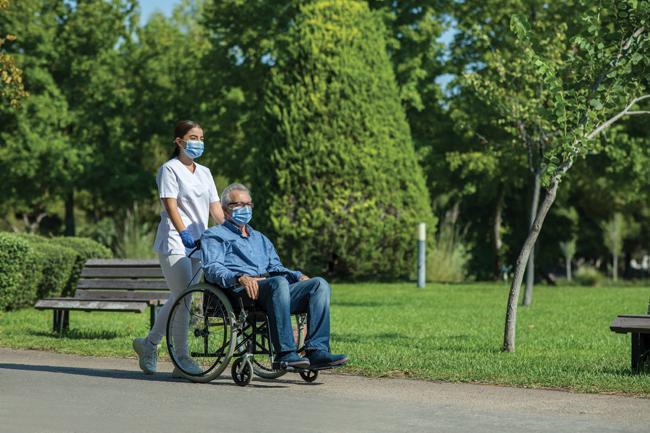 Nurse taking patient for a stroll in garden